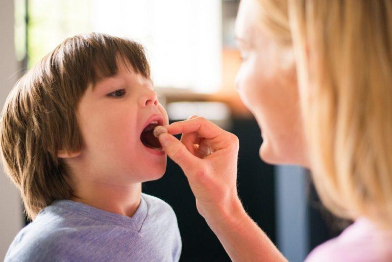 Ребенку дают таблетку