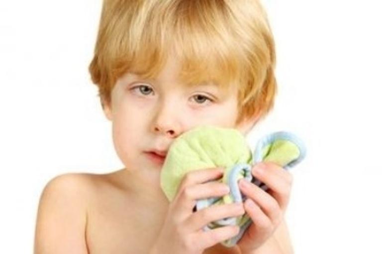 Ребенок прикладывает холодный компресс к щеке